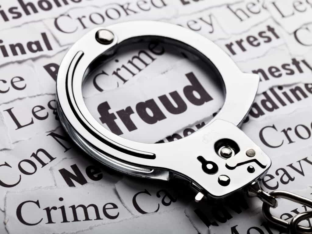 The Word Fraud Encircled by Handcuffs